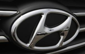 Kia cars are reflected in the Hyundai auto logo at a shipping yard in Pyeongtaek