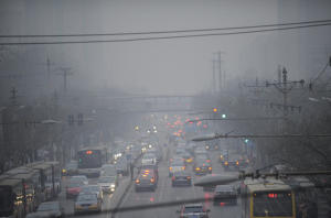 Cars pass along a road in thick smog in